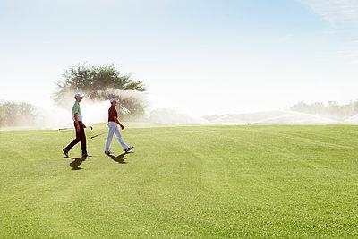 Friends walking on golf course near sprinklers - p555m1472900 by Kolostock