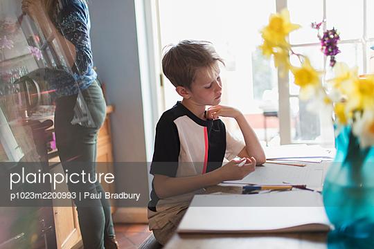 Boy doing homework at kitchen table - p1023m2200993 by Paul Bradbury