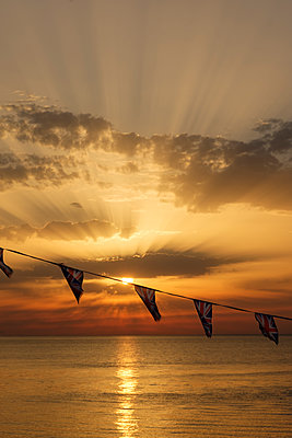 Union Jack bunting against a seaside sunset - p1228m2013349 by Benjamin Harte