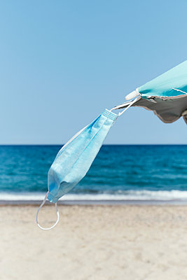 Blue face mask hanging from a blue parasol on the beach - p1423m2203348 by JUAN MOYANO