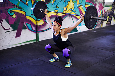 A female athlete trains in a crossfit gym.  - p343m1184145 by Josh Campbell