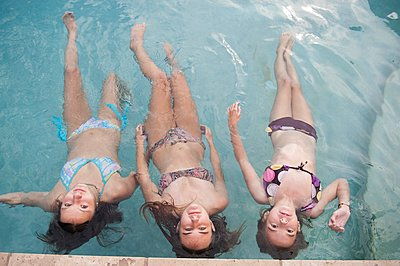 Girls floating in swimming pool - p555m1409123 by Shestock