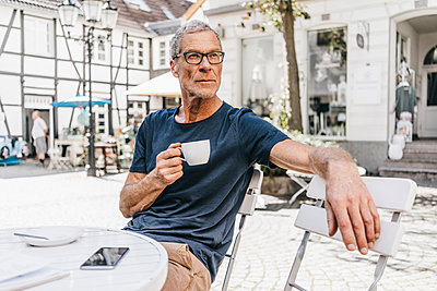 Mature man in sidewalk cafe drinking a cup of coffee - p586m1171814 by Kniel Synnatzschke