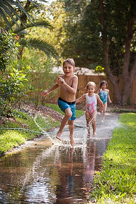 Children running in water on sidewalk - p924m1125684f by Kinzie Riehm