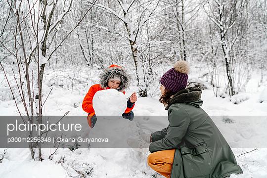 Girl with teenage sister making snowman in forest - p300m2256348 by Oxana Guryanova