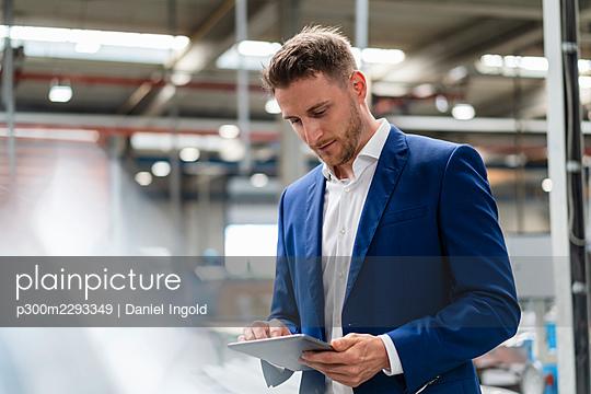 Male professional in blue blazer using digital tablet in factory - p300m2293349 by Daniel Ingold