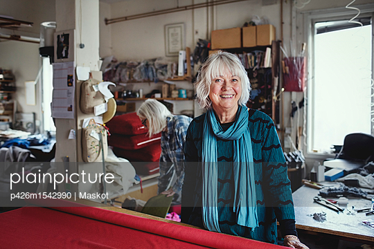 Portrait of smiling senior female standing at workbench in workshop - p426m1542990 by Maskot