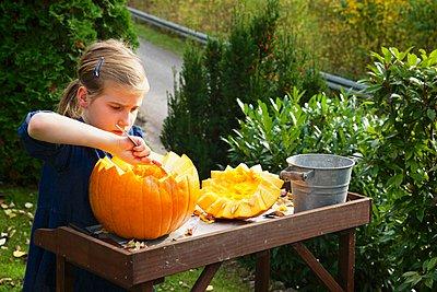 Girl carving Jack O'Lantern - p1026m906823f by AlexandraDost