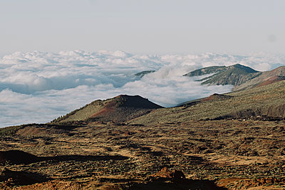 Pulled back view of volcanic landscape over the clouds - p1166m2124312 by Cavan Images