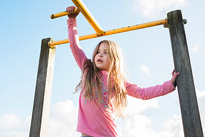 Young girl on playground equipment at the park - p1166m2213058 by Cavan Images