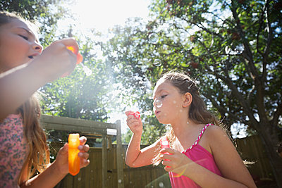 Girls blowing bubbles in sunny backyard - p1192m1183938 by Hero Images