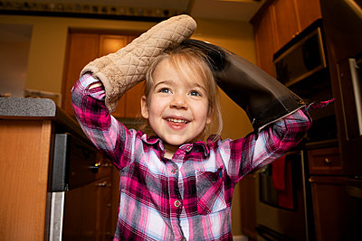 Portrait of a young girl playing with oven mitts - p1480m2148163 by Brian W. Downs