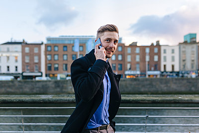 Ireland, Dublin, portrait of young businessman telephoning with smartphone - p300m1101333f by Boy photography