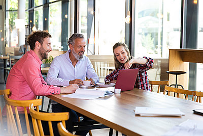 Casual business people having a meeting in a cafe - p300m2140360 von Florian Küttler