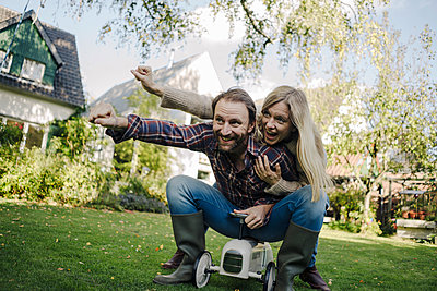 Laughing couple, pretending to fly on a toy car in the garden - p300m2166714 by Kniel Synnatzschke