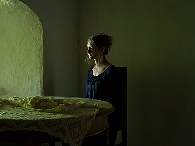 Woman sitting at table - p945m1497313 by aurelia frey