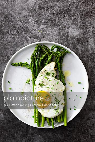 Asparagus and fried egg on a plate - p300m2114203 von Giorgio Fochesato