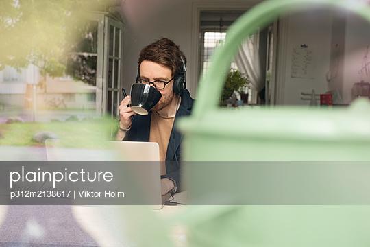 Mid adult man using laptop - p312m2138617 by Viktor Holm