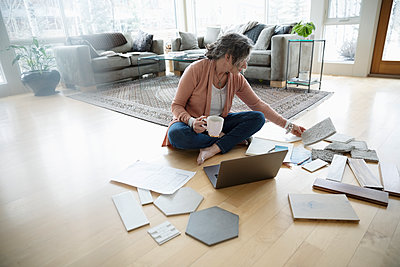 Senior woman redecorating, looking at swatches on floor - p1192m2088256 by Hero Images