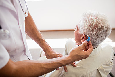 Nurse giving hearing device to a senior man in a retirement home - p1315m1186290 by Wavebreak