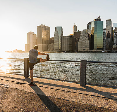 USA, Brooklyn, man doing stretching exercises in front of Manhattan skyline in the evening - p300m1205705 by Uwe Umstätter