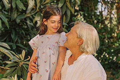 Smiling senior woman looking at cute granddaughter against plants in yard - p300m2206693 by Eloisa Ramos