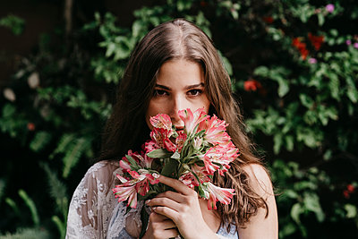 Young woman smelling fresh flowers - p300m2293379 by MORNINGVIEW AGENCY