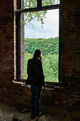 Frau am Fenster eines alten Gebäudes - p491m1119194 von Ernesto Timor