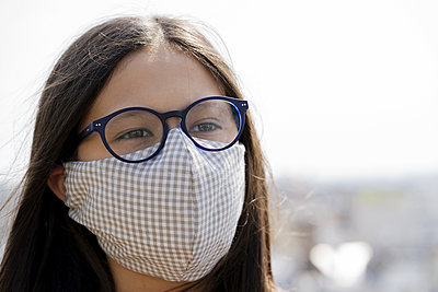 Close up of teenage girl wearing homemade face mask outdoors - p623m2186250 by Frederic Cirou