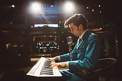 Rockabilly musician playing electric piano on stage - p1192m1567141 by Hero Images