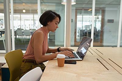 Businesswoman using laptop at desk in office - p1315m2091115 by Wavebreak