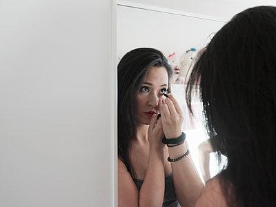 Junge Frau trägt Make-Up auf - p1383m2045091 von Wolfgang Steiner