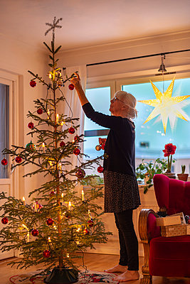 Woman dressing Christmas tree - p1418m2044775 by Jan Håkan Dahlström