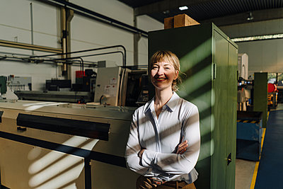 Portrait of a smiling businesswoman leaning against a cabinet in a factory - p300m2171116 by Kniel Synnatzschke