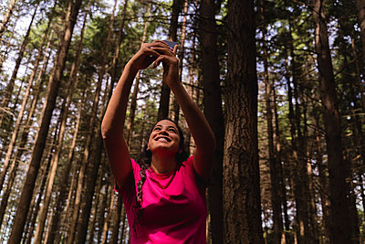 Smiling female hiker taking selfie through mobile phone with trees in background at forest - p300m2290530 by Francesco Morandini