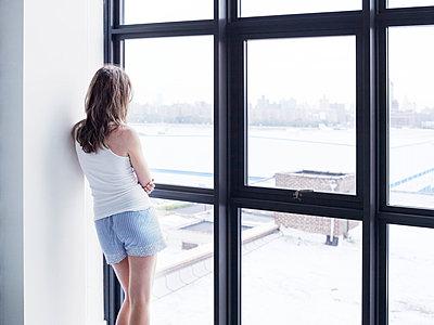 Girl looking through window - p312m992987f by Anna Kern