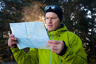 Mid adult man reading map in forest - p426m803202f by Katja Kircher