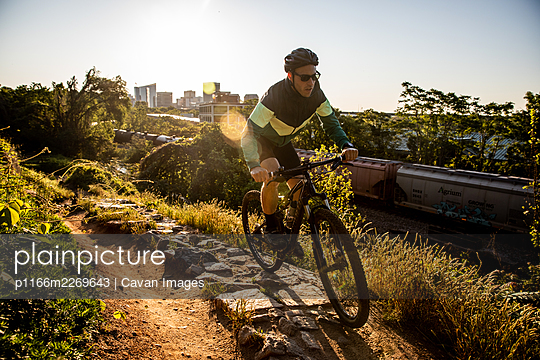 Mountain biker at sunrise with Richmond skyline in the background. - p1166m2269643 by Cavan Images