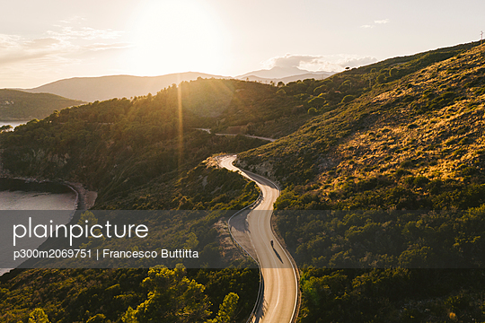 Italy, Elba Island, biker on coastal road against the sun, aerial view with drone - p300m2069751 by Francesco Buttitta