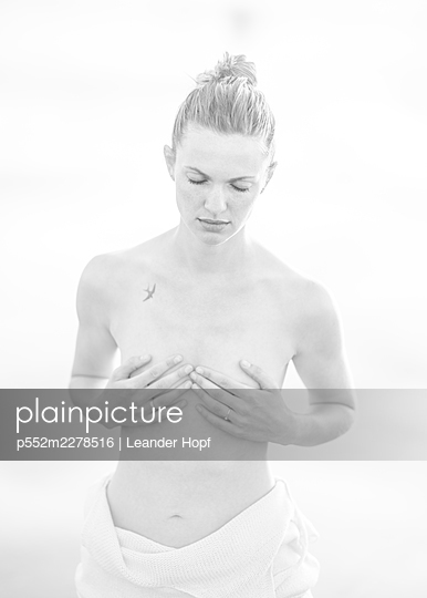 Woman covering her breasts with her hands, portrait - p552m2278516 by Leander Hopf