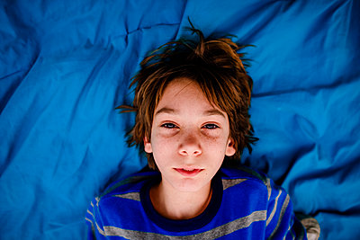 High angle portrait of boy lying on bed at home - p1166m2112811 by Cavan Images
