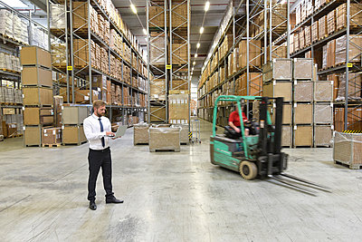 Businessman with laptop in warehouse and worker on forklift - p300m1499330 by lyzs