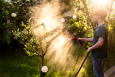 Boy using garden hose for watering tree in the garden - p300m1588189 von Sandra Roesch