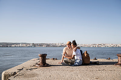 Young couple sitting on pier at the waterfront using cell phone, Lisbon, Portugal - p300m2144909 by Uwe Umstätter