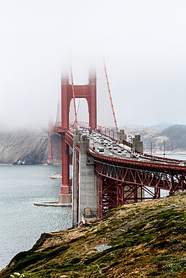 View of Golden Gate Bridge over bay of water during foggy weather, San Francisco, California, USA - p301m1180728 by Britta Wendland