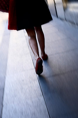 Rearview legs and feet of woman walking along city street - p597m1488677 by Tim Robinson