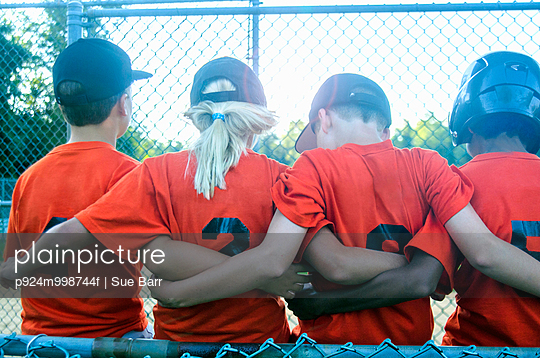 Young baseball players with arms around each other, rear view