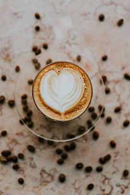 Overhead view of cappuccino with roasted coffee beans on table at cafe - p1166m2025186 by Cavan Images