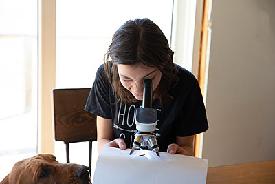 Tween girl looking into microscope with dog looking on - p1166m2236930 by Cavan Images