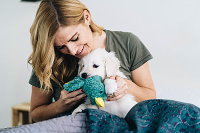 Smiling woman playing with Golden Retriever dog at home - p300m2250488 by Daniel González